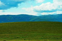 Ajardine com montanhas, prado e o céu nebuloso Foto de Stock