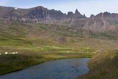 Ajardine com montanhas, rio e monte de feno, Islândia Foto de Stock