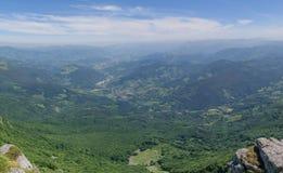 ajardine com montes e o céu verde do floresta e o azul Fotografia de Stock