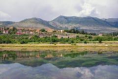 Ajardine com montes, montanhas e a cidade pequena no banco de rio é refletida na água Bósnia e Herzegovina, rio de Trebisnjica Imagem de Stock Royalty Free
