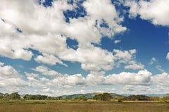 Ajardine com Mountain View, o céu azul e as nuvens bonitas. Imagens de Stock