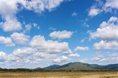 Ajardine com Mountain View, o céu azul e as nuvens bonitas. Fotografia de Stock