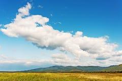 Ajardine com Mountain View, o céu azul e as nuvens bonitas. Imagem de Stock Royalty Free