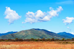 Ajardine com Mountain View, o céu azul e as nuvens bonitas Fotografia de Stock