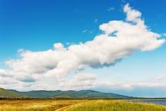 Ajardine com Mountain View, o céu azul e as nuvens bonitas Imagem de Stock