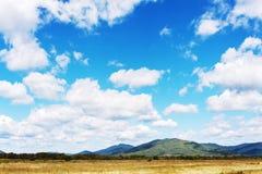 Ajardine com Mountain View, o céu azul e as nuvens bonitas Imagem de Stock Royalty Free
