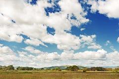 Ajardine com Mountain View, o céu azul e as nuvens bonitas Imagens de Stock Royalty Free