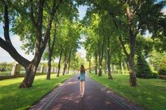 Ajardine com mulher, árvores, grama verde, caminho Fotografia de Stock