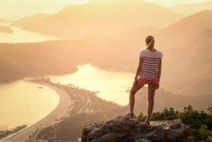 Ajardine com mulher, mar, cumes da montanha e o céu alaranjado Fotos de Stock Royalty Free