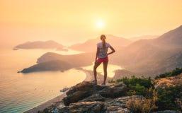 Ajardine com mulher, mar, cumes da montanha e o céu alaranjado Imagem de Stock