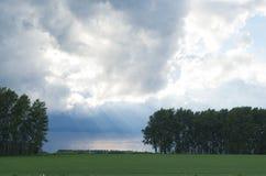 Ajardine com nuvens, chuva e sol na terra Foto de Stock Royalty Free