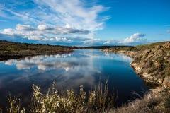 Ajardine com nuvens e reflexões no rio Fotografia de Stock Royalty Free