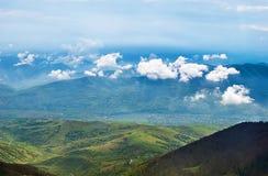 Ajardine com nuvens, montanhas, o céu azul e a vila Imagem de Stock Royalty Free