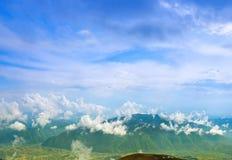 Ajardine com nuvens, montanhas, o céu azul e a vila Fotos de Stock Royalty Free