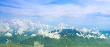Ajardine com nuvens, montanhas, o céu azul e a vila Carpathi Imagem de Stock