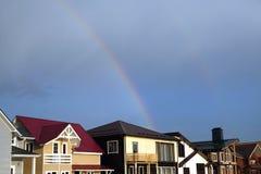 Ajardine com o arco-íris após a chuva acima das casas da vila da casa de campo Fotos de Stock Royalty Free