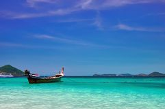 Ajardine com o barco de madeira do longtail da pesca no mar tropical do meio-dia com água de turquesa Conceito do Seascape da vid Fotografia de Stock