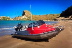Ajardine com o barco de motor vermelho e o Sandy Beach Imagem de Stock Royalty Free
