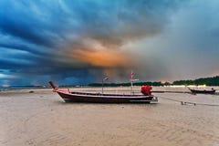 Ajardine com o barco tradicional tailandês sob o céu dramático Fotos de Stock Royalty Free