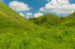Ajardine com o céu nebuloso azul sobre a ravina coberto de vegetação com as ervas verdes em Ucrânia central Fotografia de Stock