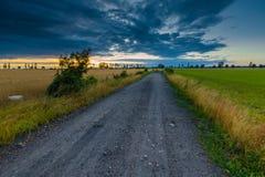 Ajardine com o céu tormentoso escuro sobre campos no crepúsculo Fotografia de Stock