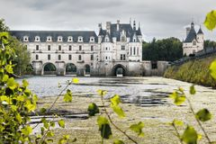 Ajardine com o castelo de Chenonceau na água com muito al verde imagem de stock royalty free