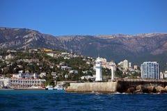 Ajardine com o farol na cidade do mar Fotos de Stock Royalty Free