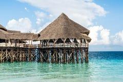 Ajardine com o hotel africano no mar no cais, Zanzibar Imagem de Stock Royalty Free