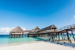 Ajardine com o hotel africano no mar no cais, Zanzibar Foto de Stock