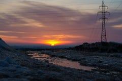 Ajardine com o lago congelado no fundo de um por do sol Imagem de Stock