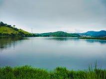 Ajardine com o lago da água azul e com reflexão das árvores que estão ao redor, da montanha no fundo e da grama no botto fotografia de stock royalty free