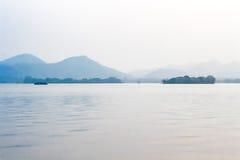 Ajardine com o lago, o barco, o pagode e as montanhas Foto de Stock Royalty Free