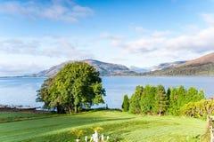 Ajardine com o lago selvagem escocês bonito e o verde das montanhas Fotografia de Stock