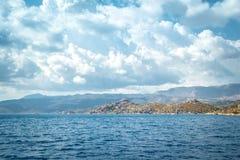 Ajardine com o mar, as montanhas e as nuvens escuras grossas em Turke Fotografia de Stock Royalty Free