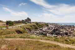 Ajardine com o motociclista embalado na estrada perto do litoral em Brittany Imagem de Stock