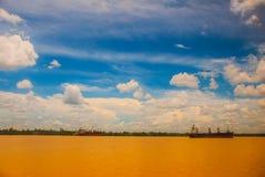 Ajardine com o Rio Amarelo e o céu azul com nuvens Velas de um navio de carga no rio Malásia, Bornéu Foto de Stock