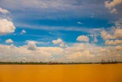 Ajardine com o Rio Amarelo e o céu azul com nuvens Velas de um navio de carga no rio Malásia, Bornéu Fotos de Stock