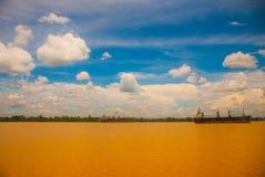 Ajardine com o Rio Amarelo e o céu azul com nuvens Velas de um navio de carga no rio Malásia, Bornéu Fotografia de Stock