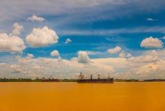 Ajardine com o Rio Amarelo e o céu azul com nuvens Velas de um navio de carga no rio Malásia, Bornéu Imagens de Stock