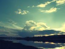 Ajardine com o rio e a ponte em um fundo do céu azul com as nuvens da noite matizadas violetas Fotos de Stock Royalty Free