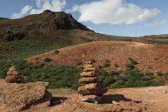 Ajardine com os dois montes de pedras vermelhos da rocha perto do Geysir Hot Springs Foto de Stock