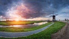 Ajardine com os moinhos de vento e o trajeto holandeses tradicionais perto dos canais da água Imagem de Stock