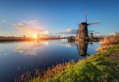 Ajardine com os moinhos de vento e o trajeto holandeses tradicionais perto dos canais da água Fotografia de Stock Royalty Free