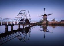Ajardine com os moinhos de vento e a ponte levadiça holandeses tradicionais no nascer do sol Foto de Stock Royalty Free