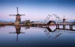 Ajardine com os moinhos de vento e a ponte levadiça holandeses tradicionais no nascer do sol Fotos de Stock Royalty Free