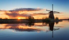 Ajardine com os moinhos de vento holandeses tradicionais no nascer do sol colorido Fotografia de Stock Royalty Free
