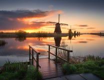 Ajardine com os moinhos de vento holandeses tradicionais no nascer do sol colorido, Imagem de Stock