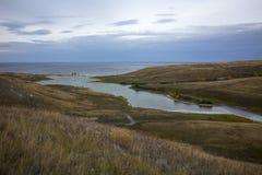Ajardine com os montes do céu e os fluxos do rio no mar Imagens de Stock Royalty Free