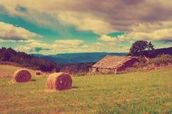 Ajardine com os pacotes colhidos da palha no campo e na casa de pedra Imagens de Stock