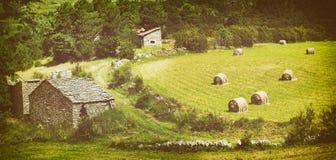 Ajardine com os pacotes colhidos da palha no campo e na casa de pedra Foto de Stock Royalty Free